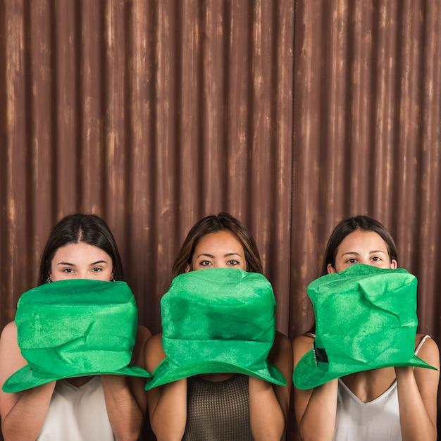 Młode kobiety z czapkami świętego patryka w pobliżu twarzy Darmowe Zdjęcia
