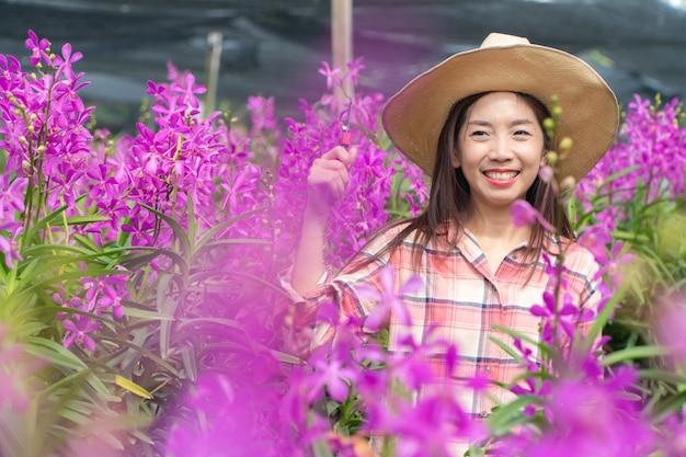 Młode Ogrodniczki Noszą Koszulę W Kratę I Kapelusz. Ręce Trzyma Nożyczki Do Cięcia Storczyków I Uśmiech. Premium Zdjęcia