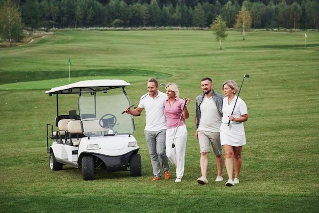 Młode Pary Przygotowują Się Do Zabawy. Grupa Uśmiechniętych Przyjaciół Doszła Do Dziury Na Wózku Golfowym Premium Zdjęcia