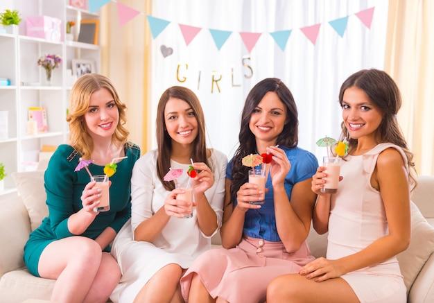 Młode piękne dziewczyny piją koktajle w domu na imprezie. Premium Zdjęcia
