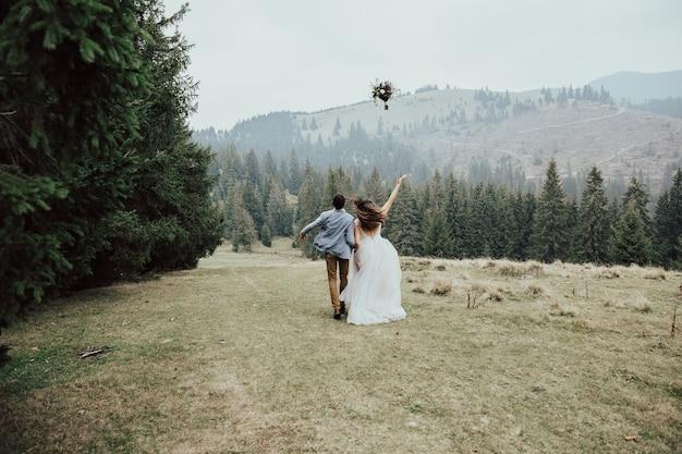 Młode Szczęśliwe Małżeństwo Biegnie W Zielonym Lesie, Rzucając Bukiet ślubny. Premium Zdjęcia