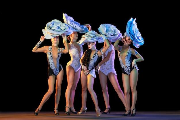 Młode Tancerki Z Ogromnymi Kwiecistymi Czapkami W Neonowym świetle Na ścianie Gradientu Darmowe Zdjęcia