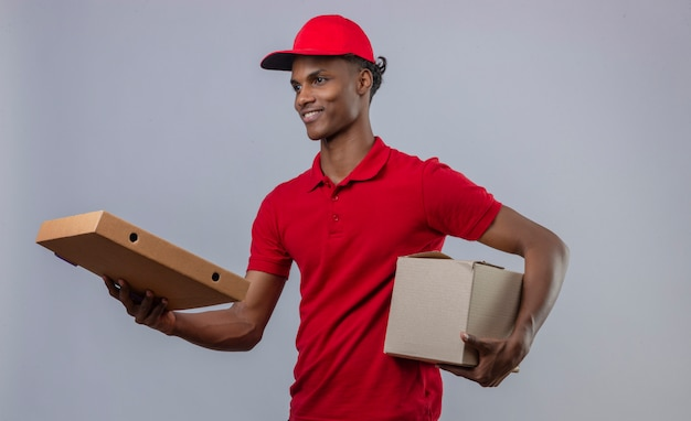 Młodego Amerykanina Afrykańskiego Pochodzenia Doręczeniowy Mężczyzna Jest Ubranym Czerwoną Polo Koszula I Nakrętki Mienia Stertę Kartony Uśmiecha Się Pizzy Pudełko Klienta I Daje Klientowi Nad Odosobnionym Bielem Darmowe Zdjęcia