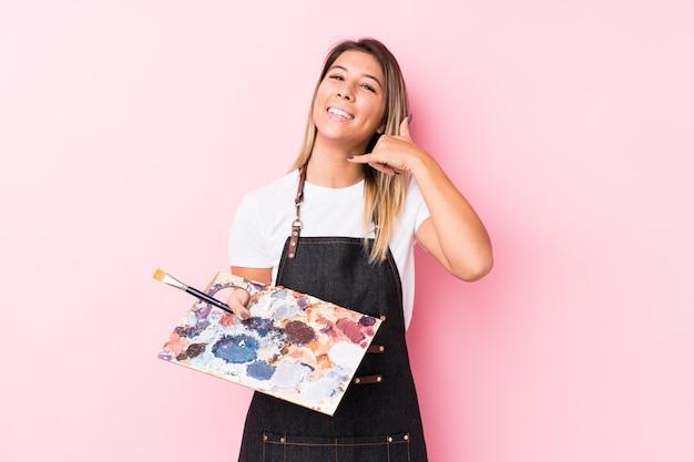 Młodego Artysty Caucasian Kobieta Trzyma Palett Odizolowywał Pokazywać Telefonu Komórkowego Wezwania Gest Z Palcami. Premium Zdjęcia