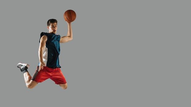 Młodego Człowieka Doskakiwanie Podczas Gdy Bawić Się Koszykówkę Z Kopii Przestrzenią Premium Zdjęcia
