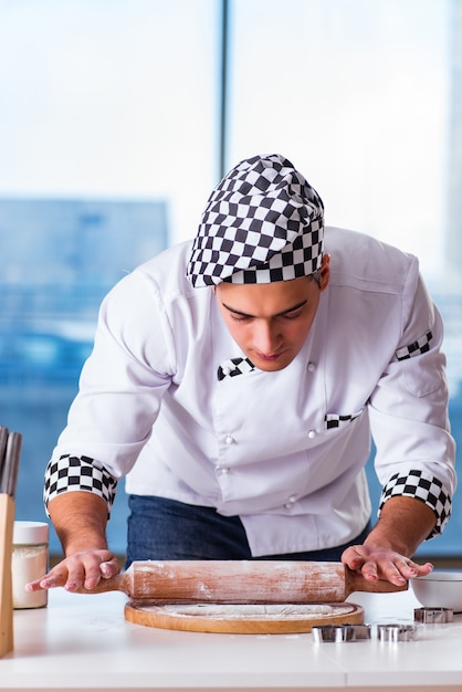 Młodego człowieka kulinarni ciastka w kuchni Premium Zdjęcia