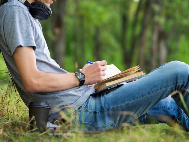 Młodego człowieka uczeń czyta książkę i przygotowywa do egzaminów siedzi na trawie w parku. Premium Zdjęcia