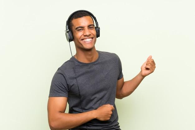 Młodego Przystojnego Mężczyzna Słuchająca Muzyka Z Wiszącą Ozdobą Nad Odosobnioną Zieleni ścianą Premium Zdjęcia