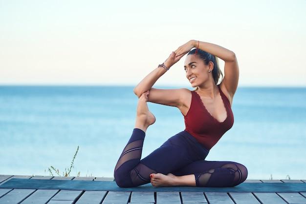 Młodej Atrakcyjnej Kobiety ćwiczy Joga Na Plaży Przy Zmierzchem. Premium Zdjęcia