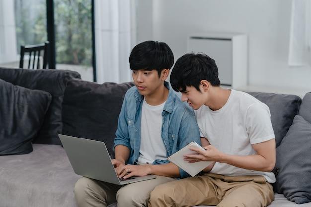 Młodej Azjatyckiej Homoseksualnej Pary Pracujący Laptop Przy Nowożytnym Domem. Asia Lgbtq + Mężczyźni Chętnie Relaksują Się Przy Użyciu Komputera I Analizują Wspólnie Swoje Finanse W Internecie, Leżąc Na Kanapie W Salonie W Domu. Darmowe Zdjęcia