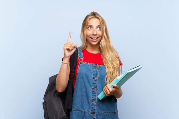 Młodej blondynki studencka kobieta wskazuje z palcem wskazującym nad odosobnioną błękit ścianą świetny pomysł Premium Zdjęcia