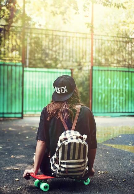 Młodej Dziewczyny Obsiadanie Na Plastikowym Pomarańczowym Grosz Shortboard Na Asfalcie W Nakrętce Darmowe Zdjęcia