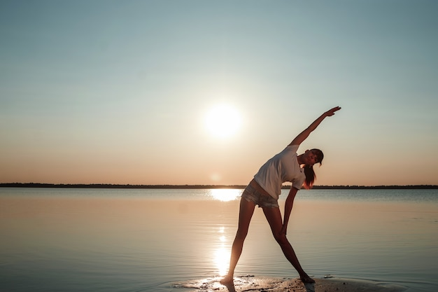 Młodej Dziewczyny Sylwetka Na Jeziorze I Piękny Zmierzch Premium Zdjęcia
