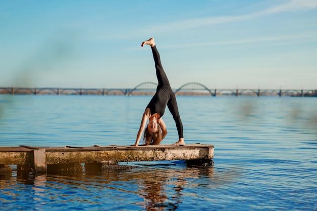 Młodej kobiety ćwiczy joga ćwiczy przy spokojnym drewnianym molem z miasta tłem. sport i rekreacja w ruchu miejskim Premium Zdjęcia