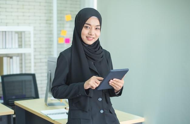 Młodej Kobiety Muzułmańska Praca W Biurze Używać Telefon Premium Zdjęcia