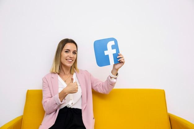 Młodej kobiety obsiadanie na żółtej kanapy mienia facebook ikonie pokazuje thumbup znaka Darmowe Zdjęcia