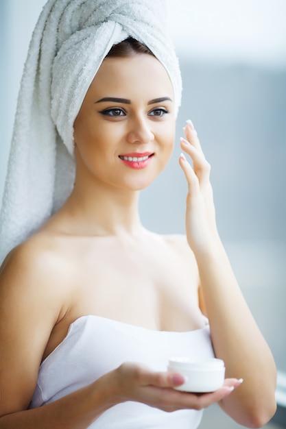 Młodej kobiety pozycja w łazience i stosować kremowy twarz w ranku Premium Zdjęcia