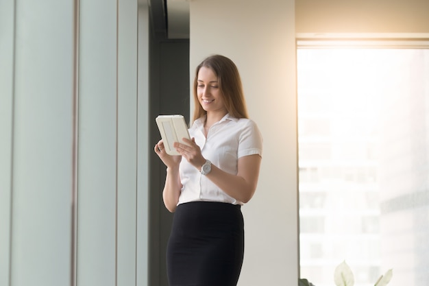 Młodej kobiety pozycja z komputerową pastylką w rękach Darmowe Zdjęcia