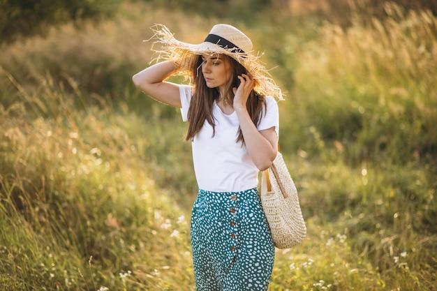 Młodej kobiety pozycja z torbą w dużym kapeluszu w polu Darmowe Zdjęcia