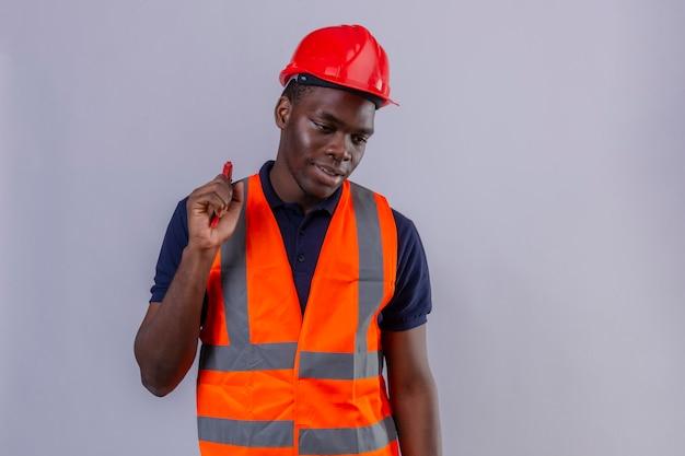 Młody Afroamerykanin Budowniczy Mężczyzna Ubrany W Kamizelkę Budowlaną I Kask Ochronny, Trzymając Klucz Nastawny Patrząc Na Bok Z Uśmiechem Na Twarzy Stojącej Darmowe Zdjęcia