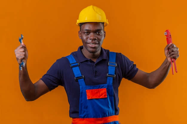 Młody Afroamerykanin Konstruktor W Mundurze Konstrukcyjnym I Hełmie Ochronnym, Trzymając Regulowane Klucze W Uniesionych Rękach Z Radosną Twarzą Stojącą Na Pomarańczowo Darmowe Zdjęcia