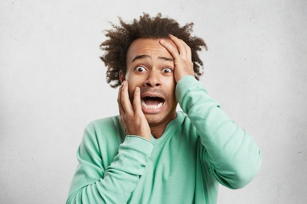 Młody Afroamerykanin Krzyczy Z Przerażenia, Trzyma Ręce Na Głowie I Szeroko Otwarte Usta Darmowe Zdjęcia