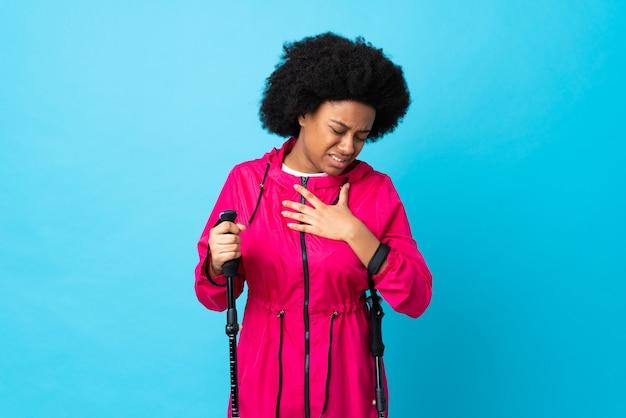 Młody Afroamerykanin Z Plecakiem I Trekking Biegunami Odizolowywającymi Na Błękitnym Tle Ma Ból W Sercu Premium Zdjęcia