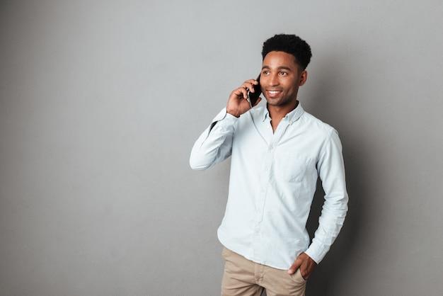 Młody Afrykański Mężczyzna Rozmawia Przez Telefon Komórkowy Stojąc Darmowe Zdjęcia