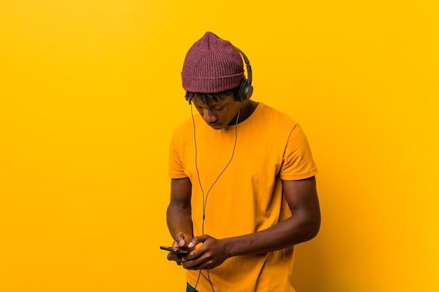 Młody Afrykański Mężczyzna Stojący Przed żółtą ścianą W Kapeluszu, Słuchając Muzyki Przez Telefon Premium Zdjęcia