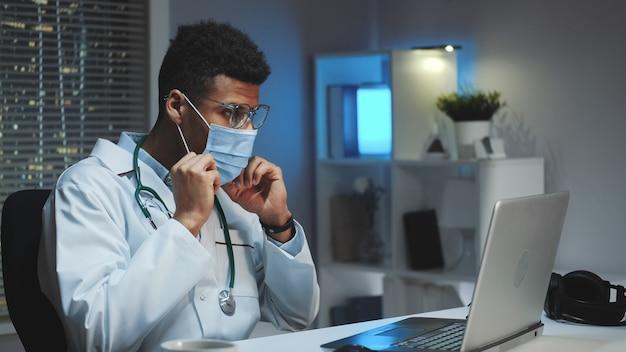 Młody Afryki Lekarz Pokazując, Jak Nosić Maskę Medyczną Przez Połączenie Wideo Na Komputerze Premium Zdjęcia
