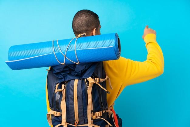 Młody Alpinista Mężczyzna Z Dużym Plecakiem Nad Odosobnioną Błękit ścianą Wskazuje Z Powrotem Z Palcem Wskazującym Premium Zdjęcia