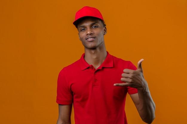 Młody Amerykanin Afrykańskiego Pochodzenia Doręczeniowy Mężczyzna Jest Ubranym Czerwoną Polo Koszula I Nakrętkę Patrzeje Ufny Robi Telefonicznemu Gestowi Dzwoni Ja Z Powrotem Podpisuje Odosobnionej Pomarańcze Darmowe Zdjęcia