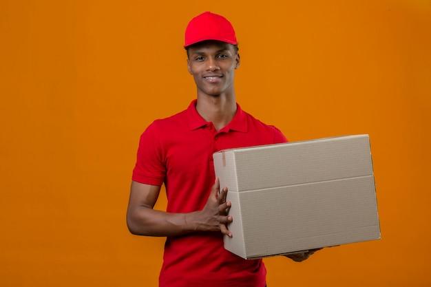 Młody Amerykanin Afrykańskiego Pochodzenia Doręczeniowy Mężczyzna Jest Ubranym Czerwoną Polo Koszula I Nakrętki Mienia Pudełka Pakunek Z Uśmiechem Na Twarzy Nad Odosobnioną Pomarańcze Darmowe Zdjęcia