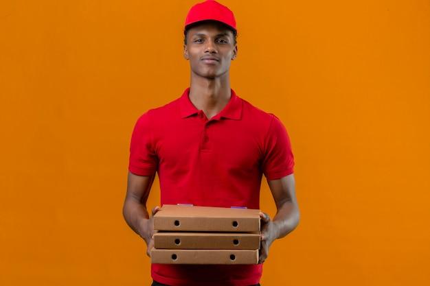 Młody Amerykanin Afrykańskiego Pochodzenia Doręczeniowy Mężczyzna Jest Ubranym Czerwoną Polo Koszula I Nakrętki Mienia Stertę Pizzy Boksuje Pozytywnego Wyrażenie Nad Odosobnioną Pomarańcze Darmowe Zdjęcia