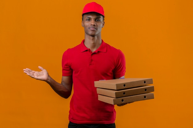 Młody Amerykanin Afrykańskiego Pochodzenia Doręczeniowy Mężczyzna Jest Ubranym Czerwoną Polo Koszula I Nakrętki Mienia Stertę Pudełek Po Pizzy Patrzeje Zmieszany I Ma Wątpliwości Nad Odosobnioną Pomarańcze Darmowe Zdjęcia