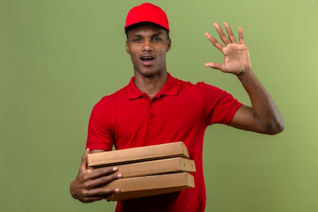 Młody Amerykanin Afrykańskiego Pochodzenia Doręczeniowy Mężczyzna Jest Ubranym Czerwoną Polo Koszula I Nakrętki Pozycję Z Stertą Pizz Pudełka Robi Powitanie Gestowi Nad Odosobnioną Zielenią Darmowe Zdjęcia