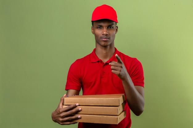 Młody Amerykanin Afrykańskiego Pochodzenia Doręczeniowy Mężczyzna Jest Ubranym Czerwoną Polo Koszula I Nakrętki Pozycję Z Stertą Pizz Pudełka Wskazuje Palec Kamera Nad Odosobnioną Zielenią Darmowe Zdjęcia