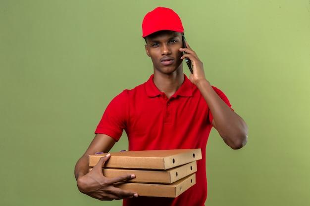 Młody Amerykanin Afrykańskiego Pochodzenia Doręczeniowy Mężczyzna Jest Ubranym Czerwoną Polo Koszula I Nakrętki Przewożenia Stertę Pizz Pudełka Podczas Gdy Mówiący Smartphone Nad Odosobnioną Zielenią Darmowe Zdjęcia