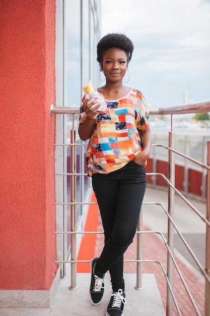 Młody Amerykanin Afrykańskiego Pochodzenia Dziewczyny Mienia Hamburger W Ona Ręki Plenerowe Premium Zdjęcia