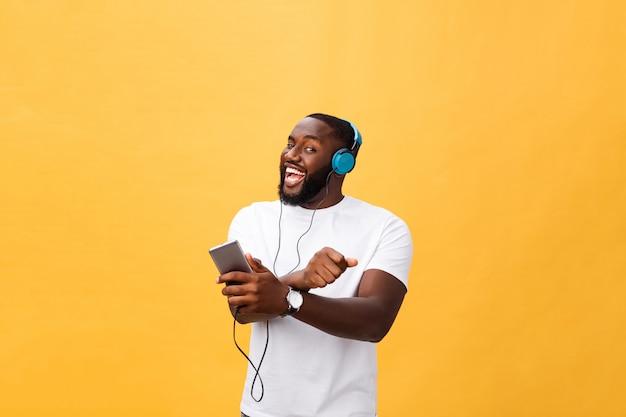 Młody amerykanin afrykańskiego pochodzenia mężczyzna jest ubranym hełmofon i cieszy się muzykę nad żółtego złota tłem Premium Zdjęcia