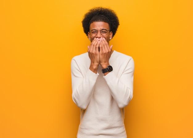 Młody amerykanin afrykańskiego pochodzenia mężczyzna nad pomarańczową ścianą śmia się z czegoś, zakrywający usta rękami Premium Zdjęcia