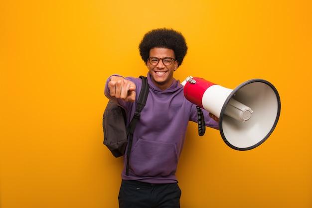 Młody amerykanina afrykańskiego pochodzenia mężczyzna holdinga megafon rozochocony i uśmiechnięty wskazywać przód Premium Zdjęcia