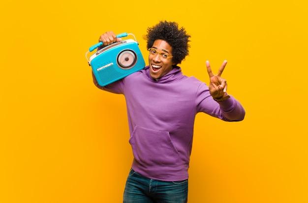 Młody amerykanina afrykańskiego pochodzenia mężczyzna z rocznika radiem przeciw pomarańczowemu b Premium Zdjęcia