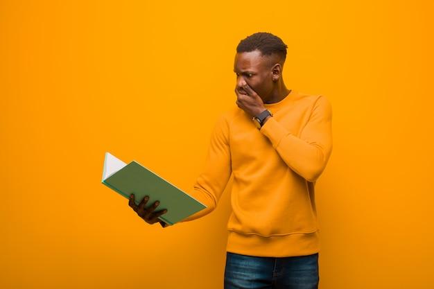 Młody Amerykanina Afrykańskiego Pochodzenia Murzyn Przeciw Pomarańcze ścianie Z Książką Premium Zdjęcia