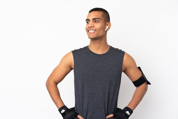 Młody Amerykanina Afrykańskiego Pochodzenia Sporta Mężczyzna Nad Odosobnioną Biel ścianą Pozuje Z Rękami Przy Biodrem I Patrzeje Stronę Premium Zdjęcia