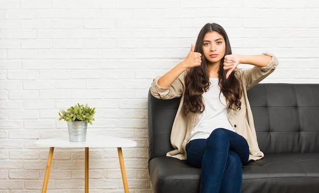Młody arabski kobiety obsiadanie na kanapie pokazuje aprobaty i kciuki zestrzela, trudny wybiera pojęcie Premium Zdjęcia