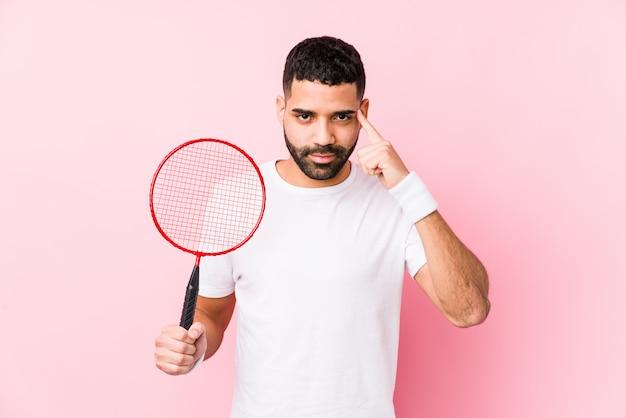 Młody Arabski Mężczyzna Bawić Się Badminton Odizolowywającą Wskazuje świątynię Z Palcem, Główkowanie, Skupiający Się Na Zadaniu. Premium Zdjęcia