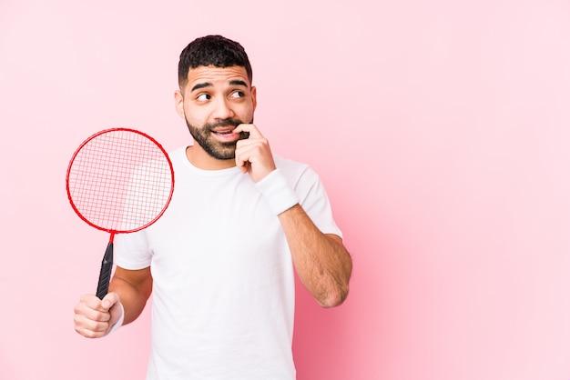Młody Arabski Mężczyzna Bawić Się Badminton Odizolowywał Zrelaksowanego Główkowanie O Coś Patrzeje Odbitkową Przestrzeń. Premium Zdjęcia