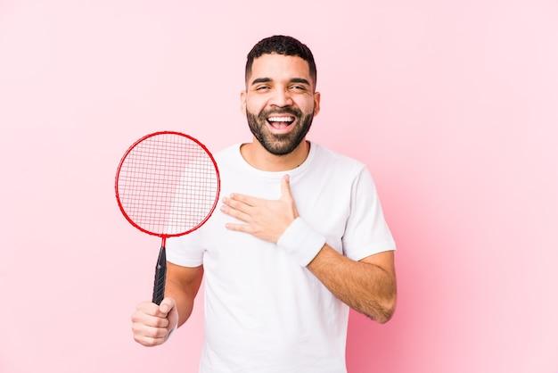 Młody Arabski Mężczyzna Gra W Badmintona Na Białym Tle śmieje Się Głośno, Trzymając Rękę Na Piersi. Premium Zdjęcia