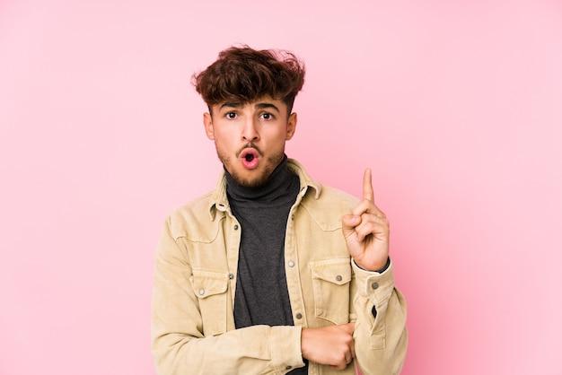 Młody Arabski Mężczyzna Pozuje W ścianie Odizolowywał Mieć Niektóre Doskonałego Pomysł, Pojęcie Twórczość. Premium Zdjęcia